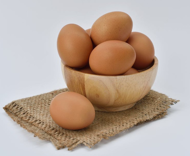 A brown wooden bowl, filled with eggs, sitting on top of brown hessian
