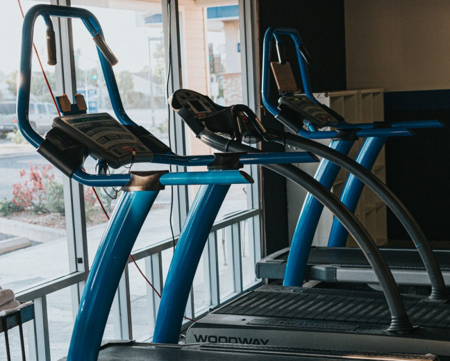 Three treadmills in a line in front of a large window