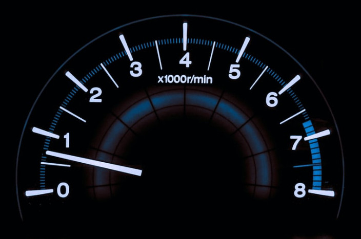 A digital rev counter featuring white numbers and arrow on a black background