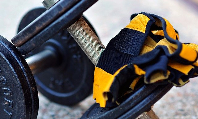 Close up shot of yellow and black gym gloves draped over a set of black and silver dumbbells
