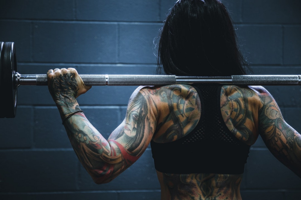 A woman facing away holding a weighted barbell over her shoulders