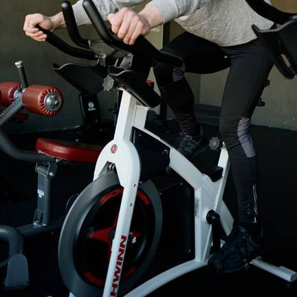 Close up of someone on a white exercise bike in a gym