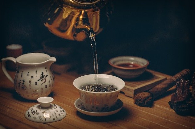 Boiling-water-being-poured-into-a-china-cup-filled-with-tea-leaves