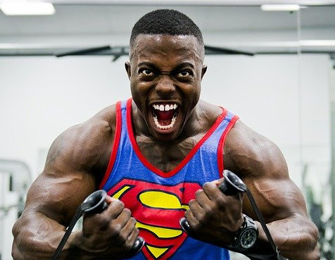 A man wearing a Superman vest tensing his upper body muscles whilst mid-exercise
