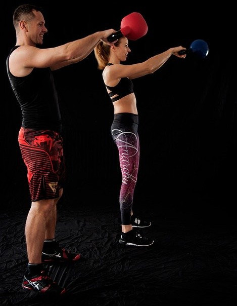 A-man-and-woman-performing-a-kettlebell-swing