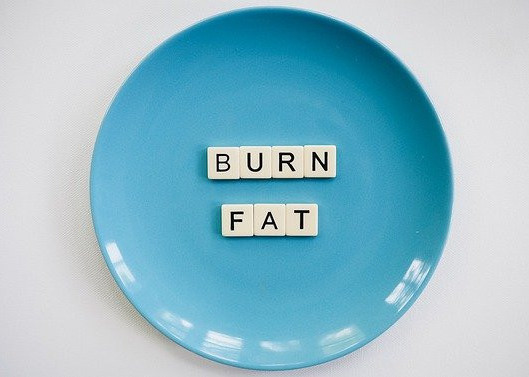 A blue plate with the words 'Burn Fat' spelled out in white tiles with black letters