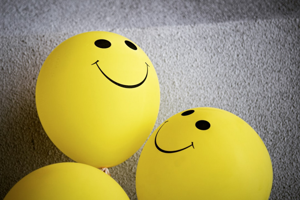 Three yellow balloons with smiley faces