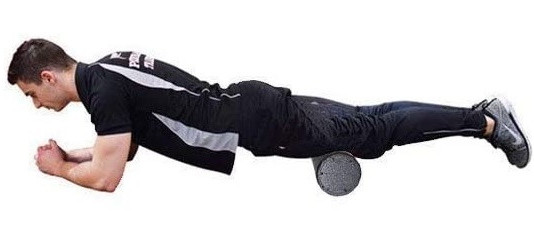 A man in black and grey gym gear performing a plank with a black foam roller underneath his legs