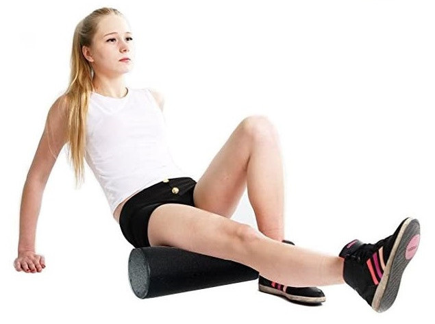 A woman in sports gear with a foam roller underneath her right leg