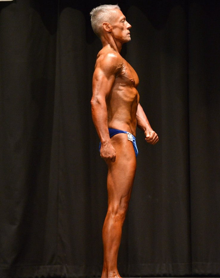 An-older-male-weight-lifter-posing-in-a-bodybuilding-competition-against-a-black-backdrop