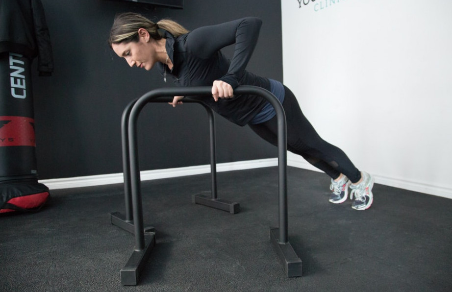 A-woman-performing-an-incline-push-up-with-two-parallel-bars