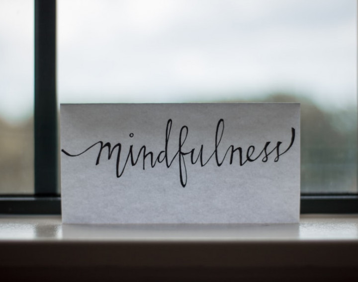 A white plaque with the word 'mindfulness' written on it in front of a window