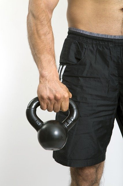The-lower-half-of-a-man-holding-a-black-kettlebell-at-his-side