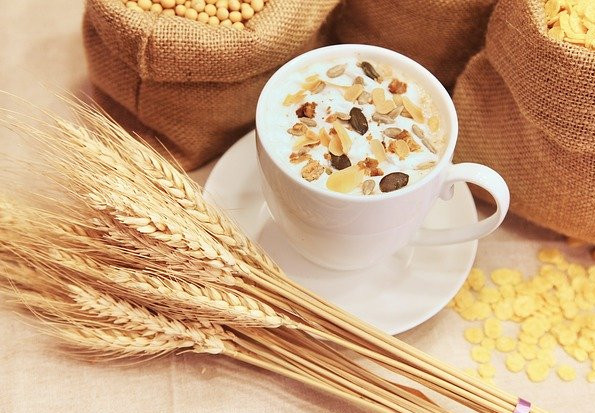 Some wheat stems, bags of grains and a white coffee cup filled with nuts