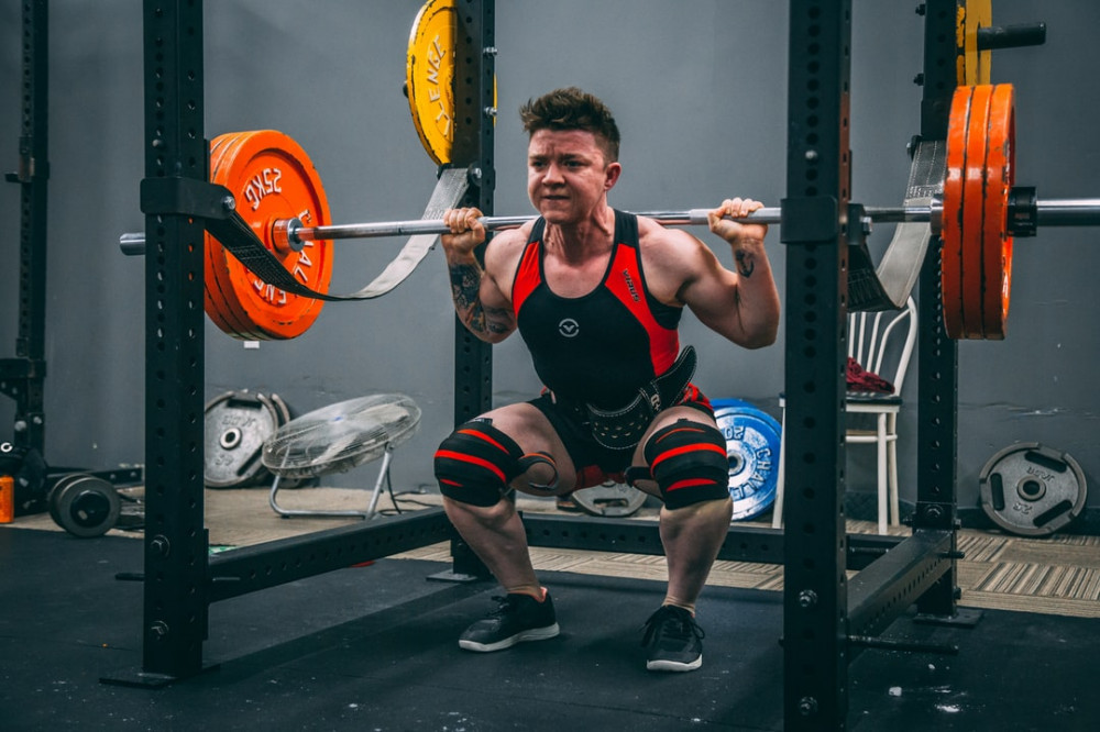 Man performing barbell squats in rack