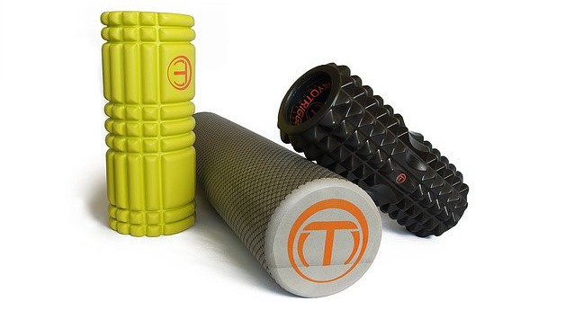 A yellow, grey and black foam roller assembled together on a white background