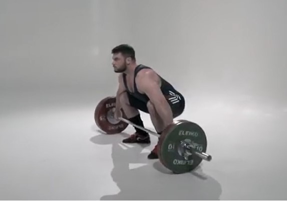 Man in the starting position to perform a barbell snatch lift