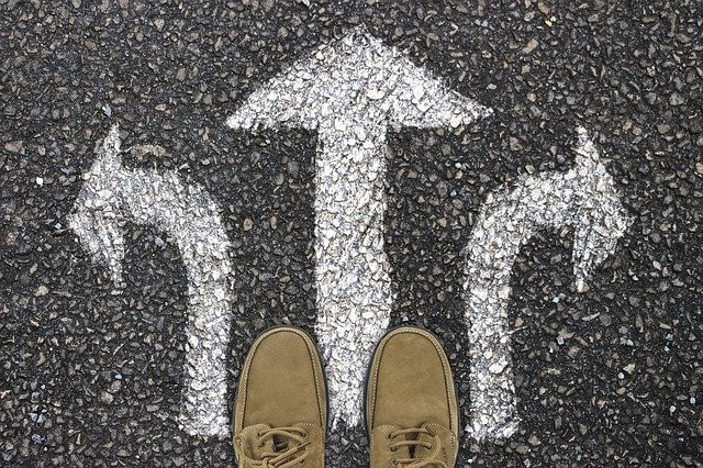 Three white arrows on tarmac and a pair of brown shoes