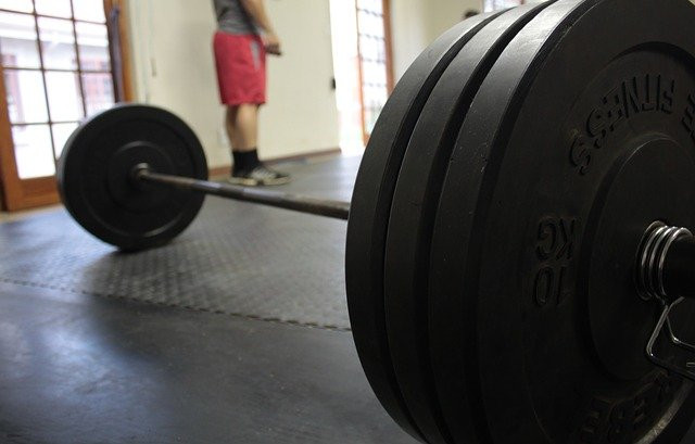 A close up of a barbell loaded with three black weight plates on each side