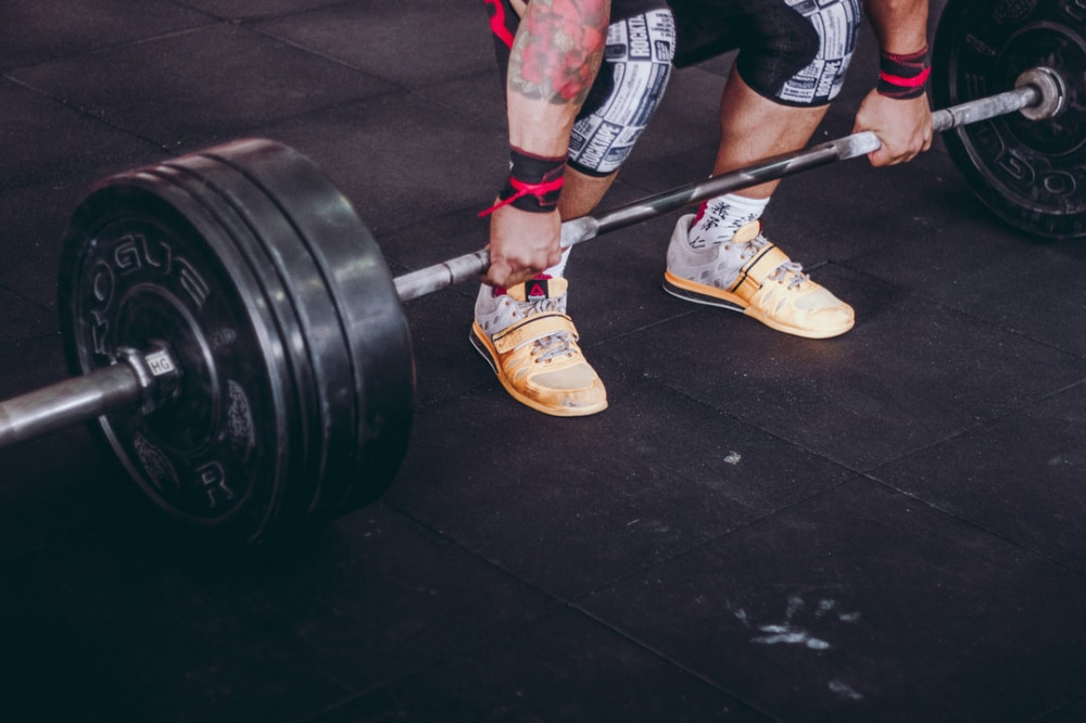 Lower half of person about to perform the snatch lift with barbell