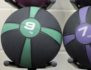 Close up of a green and black medicine ball on a black gym rack