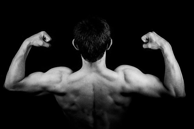 Black and white image of a man flexing his back and arm muscles
