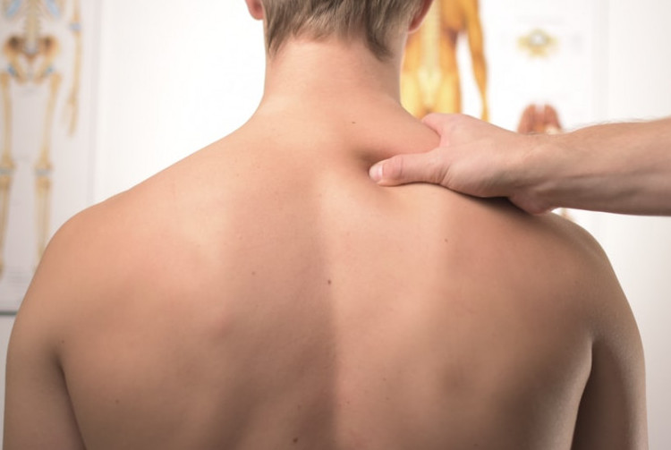 Picture of a hand massaging a man's back