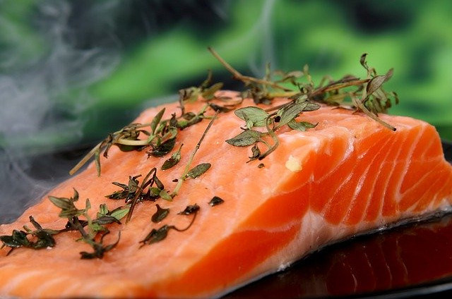 A plate of raw pink salmon scattered with herbs