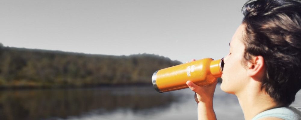 image woman drinking water at lake