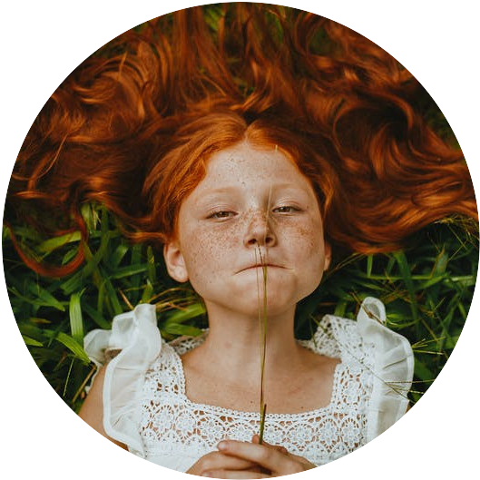Redheaded girl lying in the grass