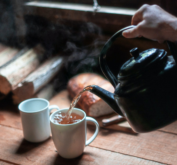 Tea being poured from Old Style Tea Pot into White Mug.