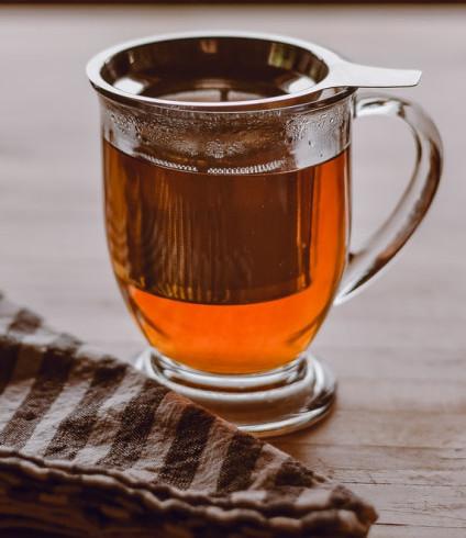 Glass Mug with Strainer inside straining Oolong Tea.