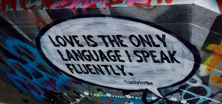 Graffiti image that says 'Love is the only language I speak fluently.'