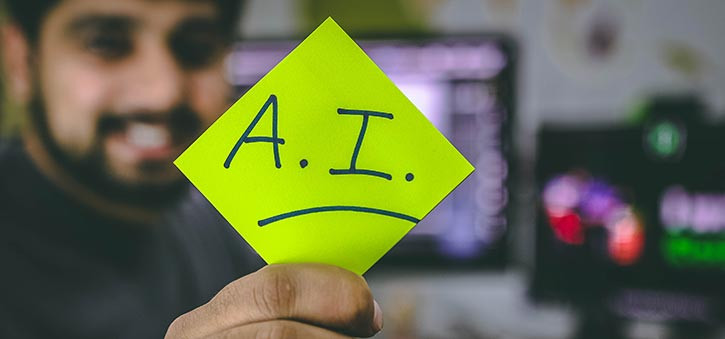 What is a chatbot definition? A chatbot developer holding a note that simply says A.I.