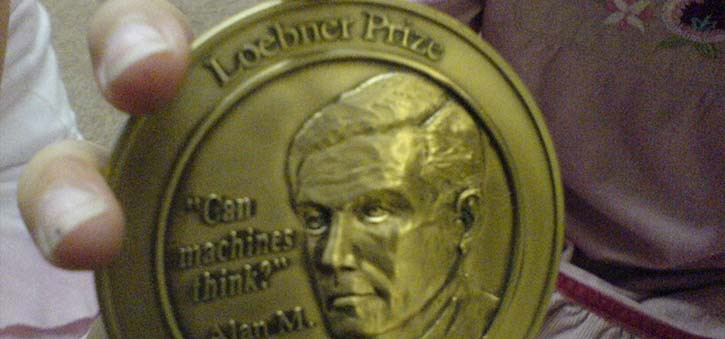 A closeup picture of someone holding the Loebner Prize Medal.