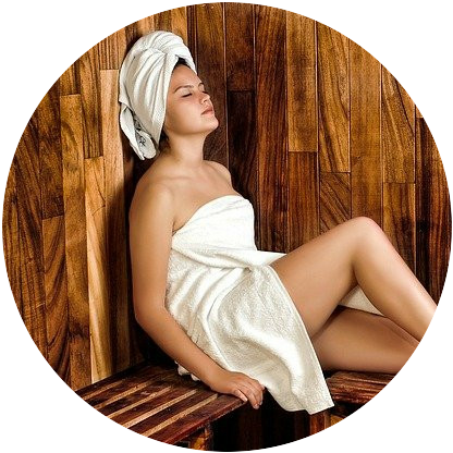 lady sitting in a sauna wrapped in a towel