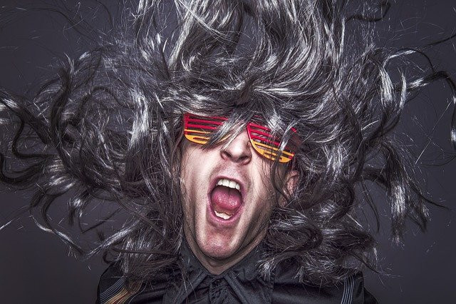 a man with long hair and party glasses
