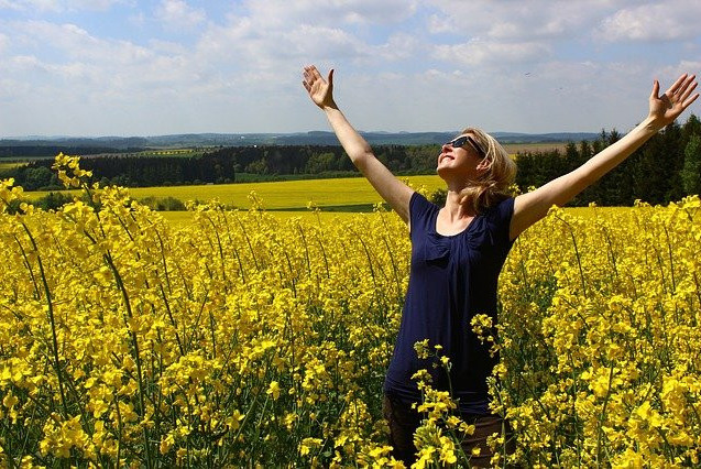 a woman in a blue dress opening wide her arms, smiling, standing in a field of yellow flowers