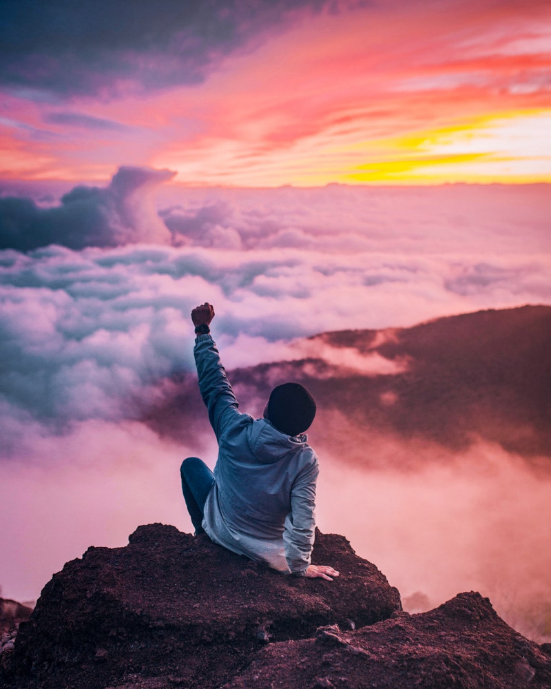 a man sitting high sbove the clouds on a mountain performing a winner gesture with his left hand