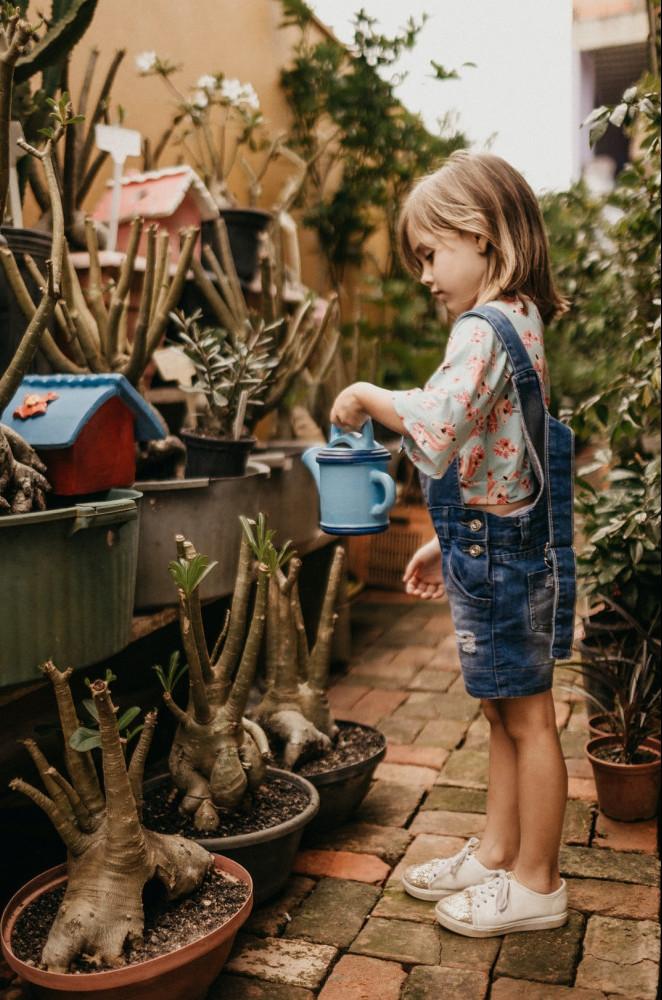 a little blond girl watering pots of flowers on a terrace