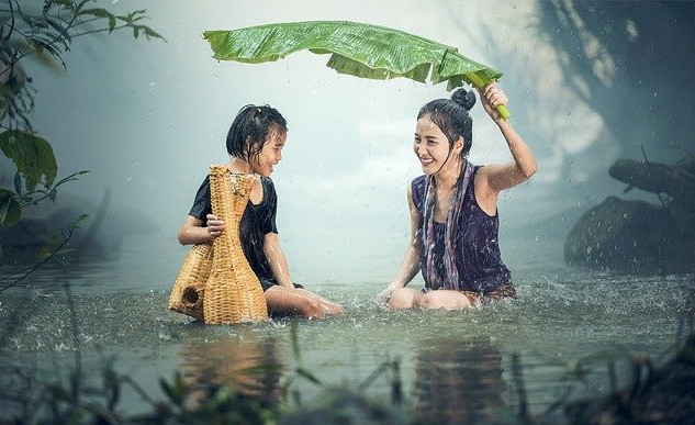 mother and daughter sitting in water, in the rain, covering themselves with a banana leaf