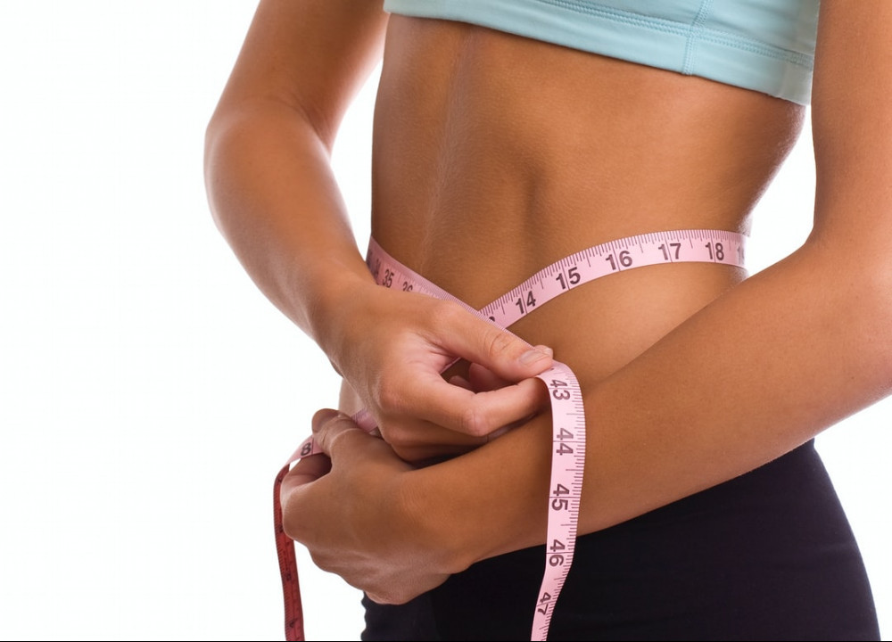 a slim woman measuring her taille