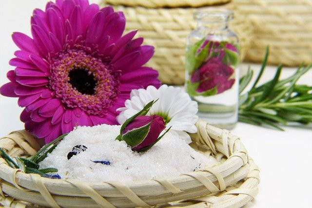 a purple flower in a little basket, a glass of water behind with a purple rose in it, and a leaf rosmarin