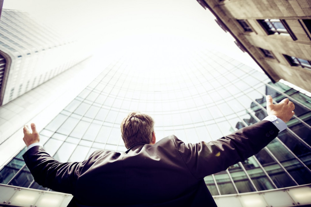 a business man joyful in front of a building, raising his arms