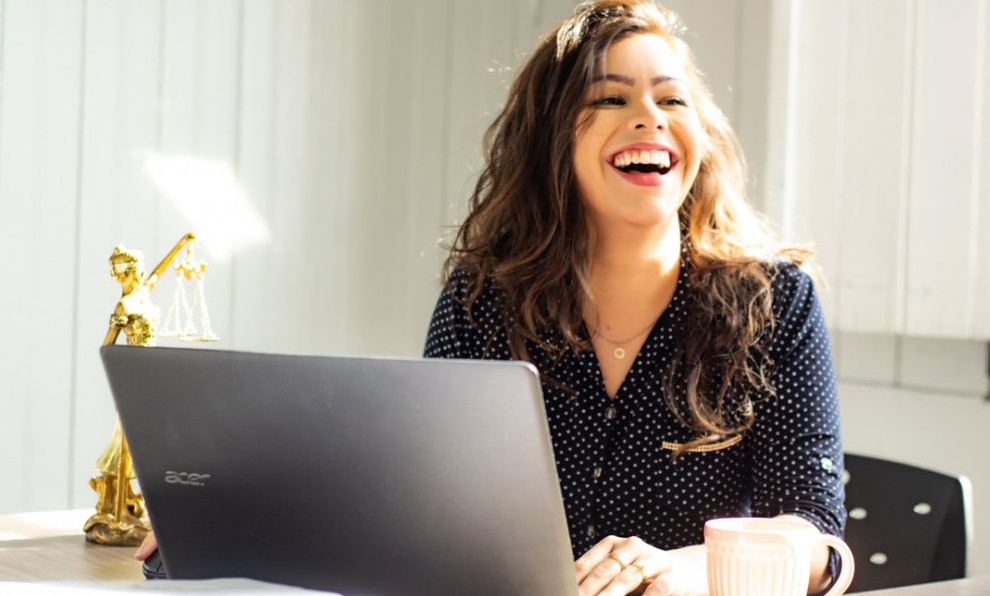 a woman laughing in front of a laptop a cup of coffee on a table, wearing a blue blouse , having long brown hair