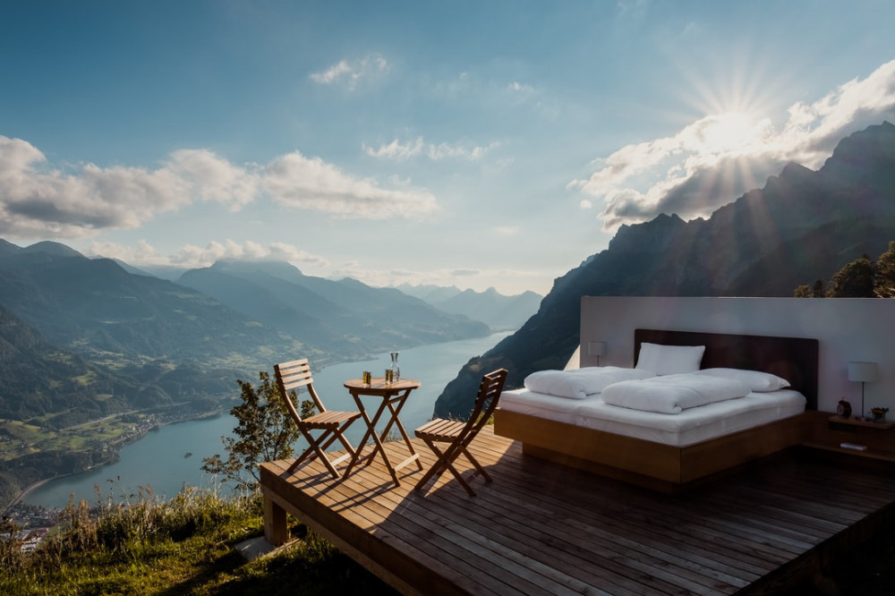 a bed and chairs and table on a terrace high up above a scenery with water and mountains