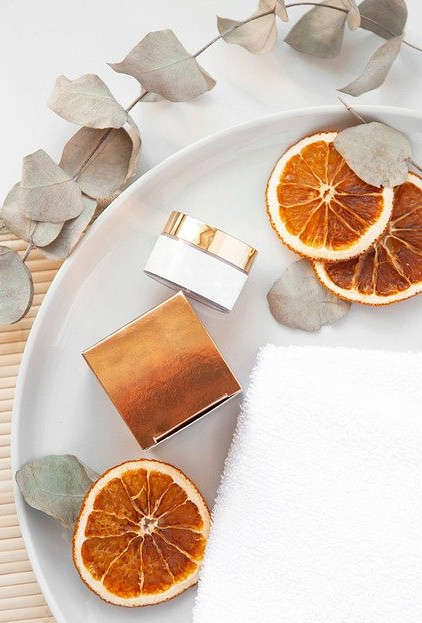 skin care , a plate with oranges cuts, a white towel and a facial cream