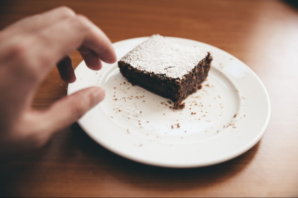 Hand reaching for sugar coated brownie