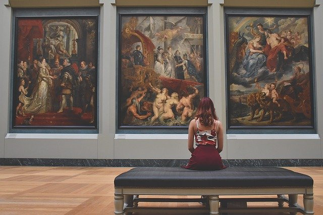 Image shows a the back side of a young lady as she stares at three paintings on display in a museum