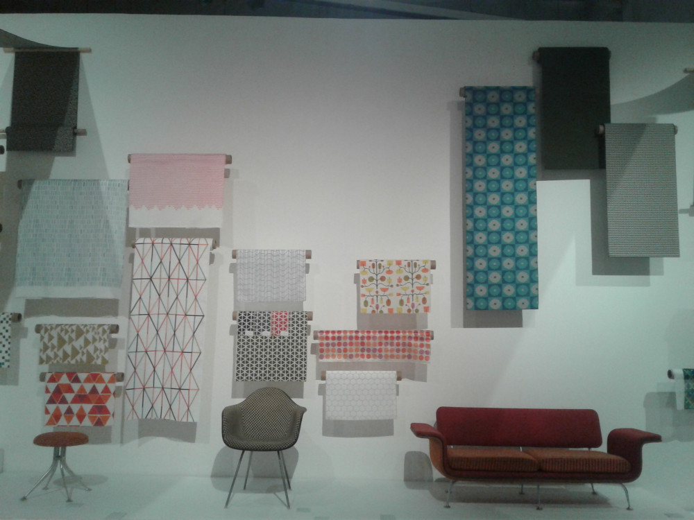 Image shows a part of the 'Alexander Girard: A Designer's Universe' exhibition. Various colorful fabrics hang from the wall and at their foot are three pieces of furniture designed by Girard.